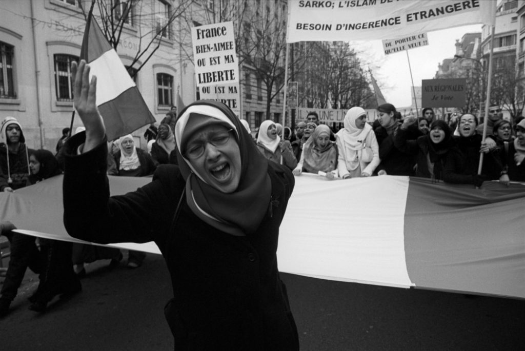 FRANCE. Paris. January 17. March in favour of wearing the Islamic hijab by girls and women in government schools and offices. A group of young women carry the French flag to stress the point they are citizens of the Republic.