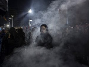 IRAN. 2015. An Iranian woman walks through a haze of smoke caused by the burning of the herb esfand. According to popular belief, this ritual drives away the evil eye.